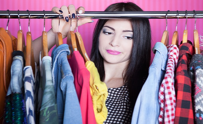 Time to refresh wardrobe young attractive disappointed woman searching for clothing in a closet